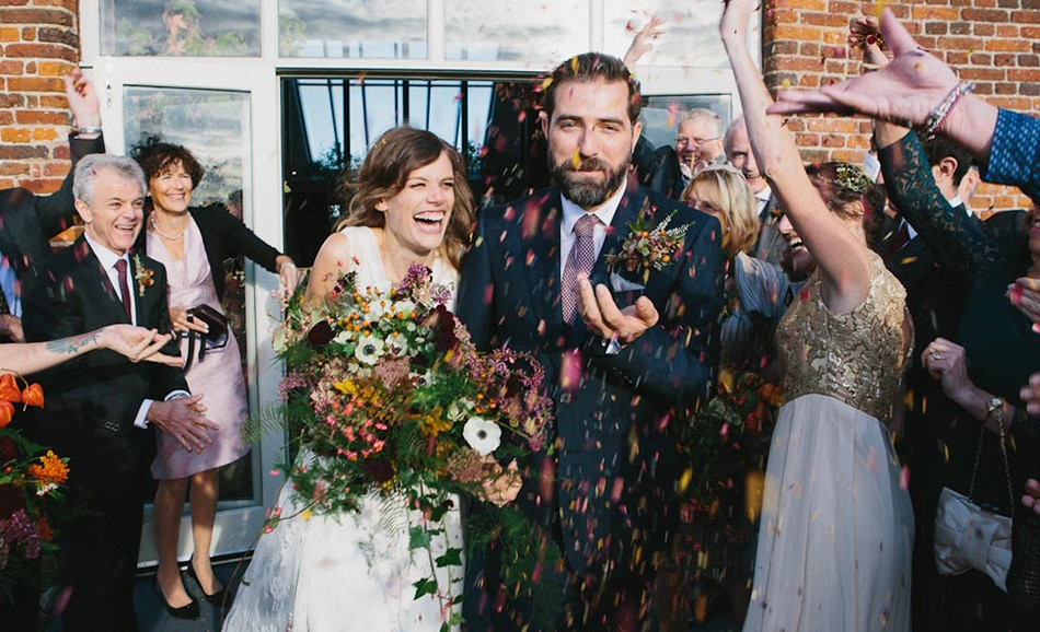 Peach and Jo's image of sheer joy as rose petal confetti showers a Godwick couple